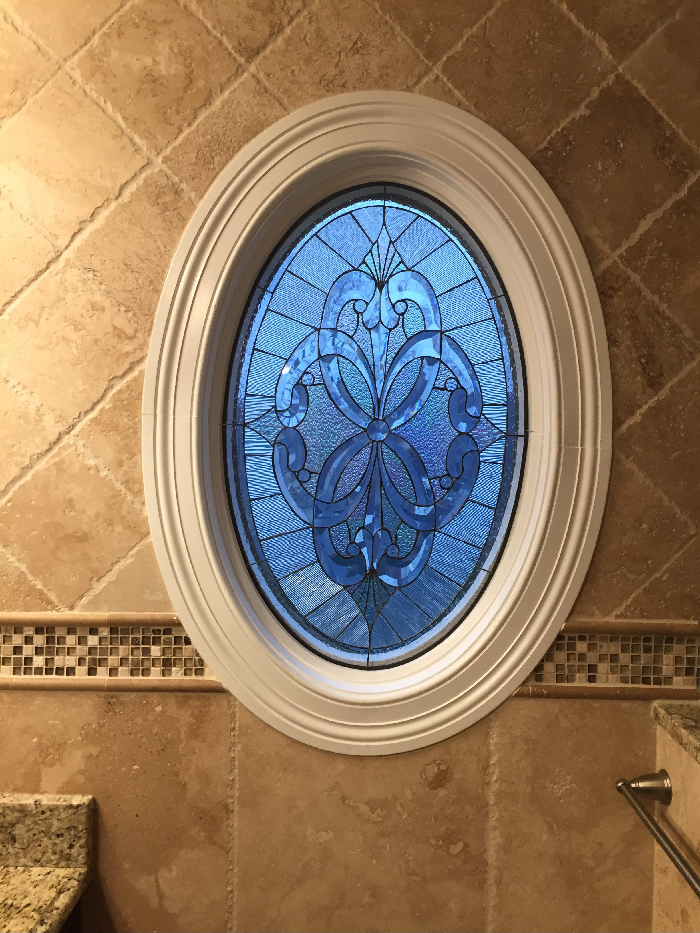 A Beautiful Oval Beveled Stained Window Insert Set Against The