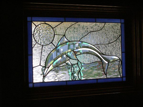 All Beveled Dolphin Stained glass window installed in wood frame