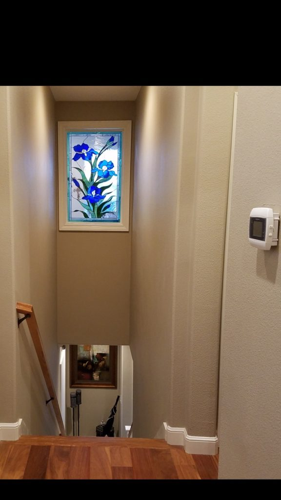 "Lovely ""iris trio"" stained glass window installed over a stairway"