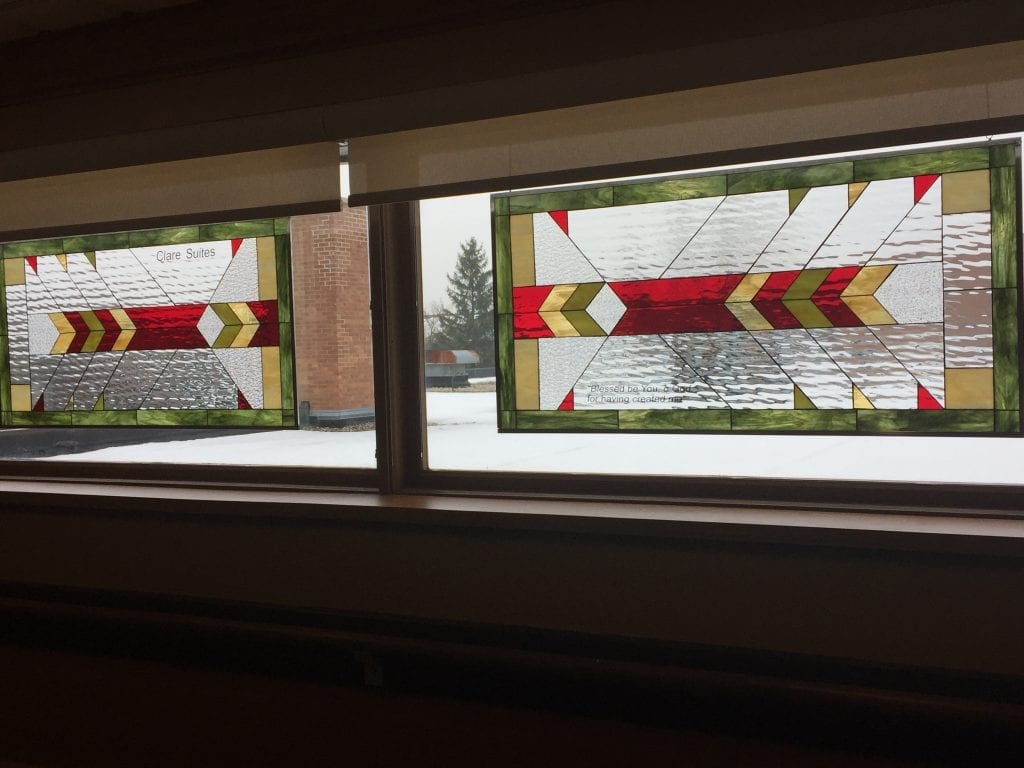 Two stained glass windows hung in a Church with personalized text
