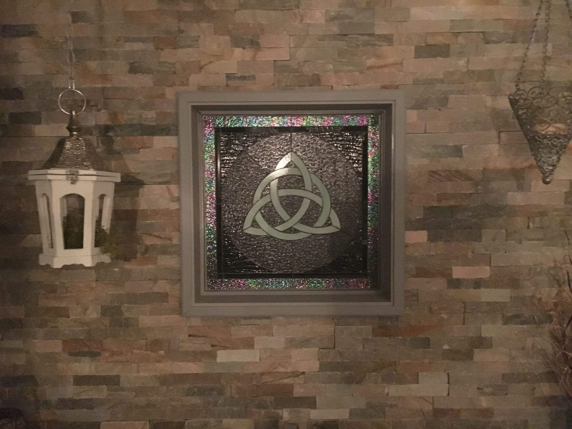 Celtic Knot Stained Glass Window Installed In A Brick Wall For Added Character