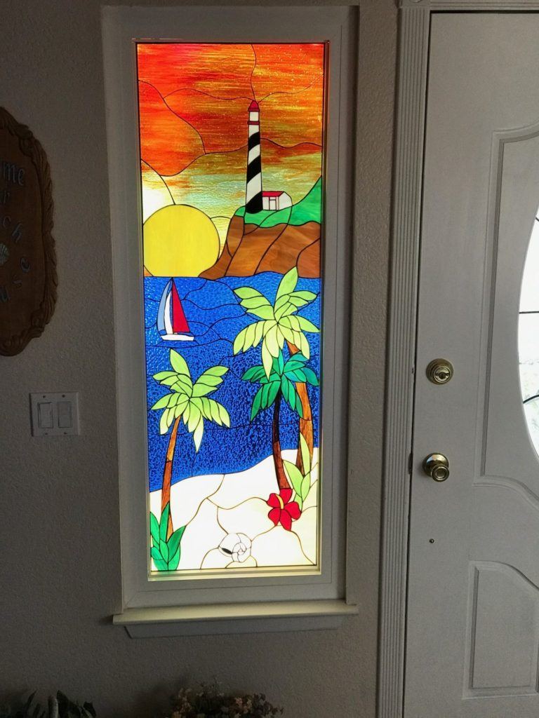 Lighthouse, palm tree and sunset stained glass side lite window added beauty and natural light