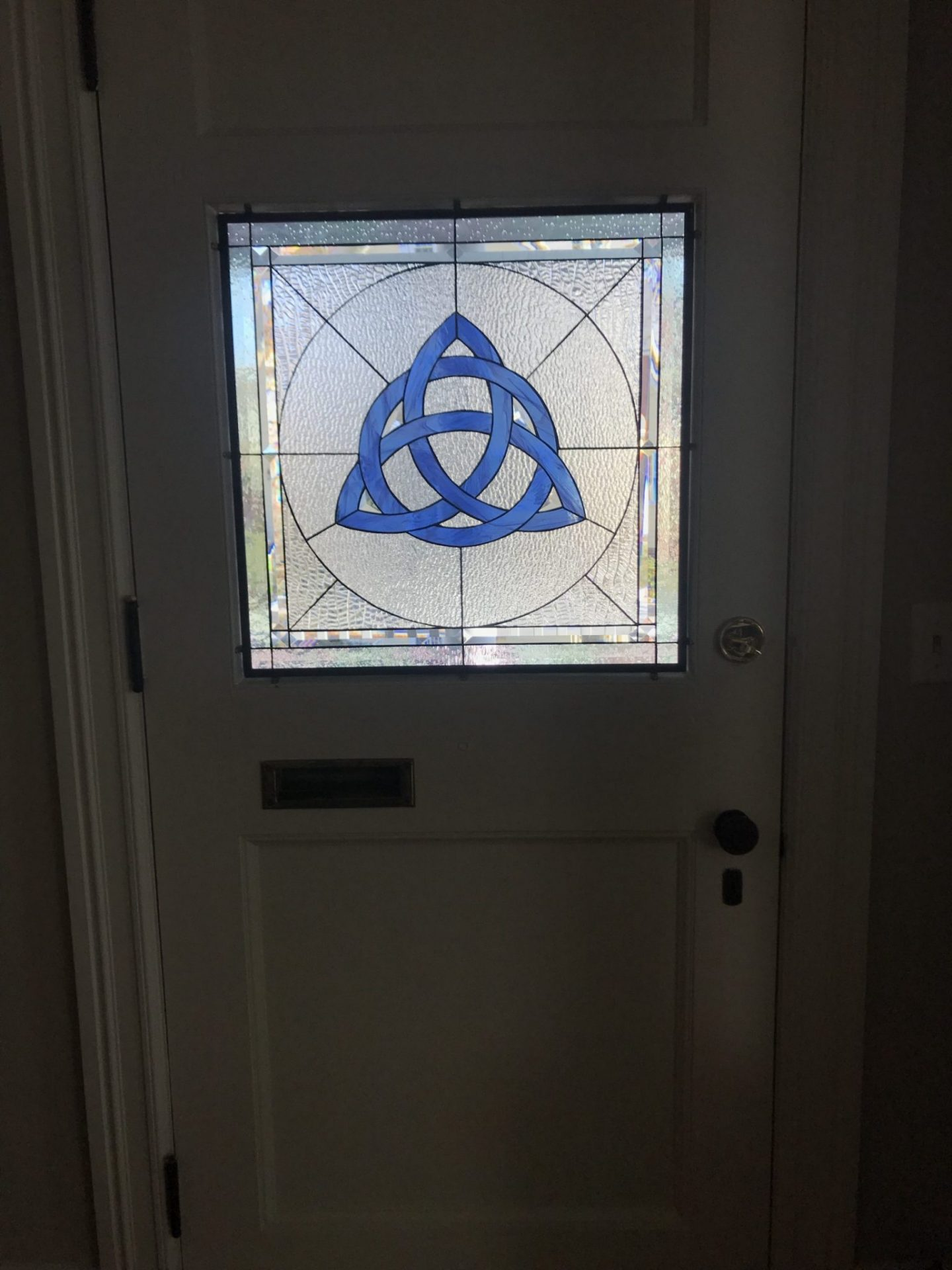 Single pane Celtic Knot stained glass inserted into a door with mirror clips