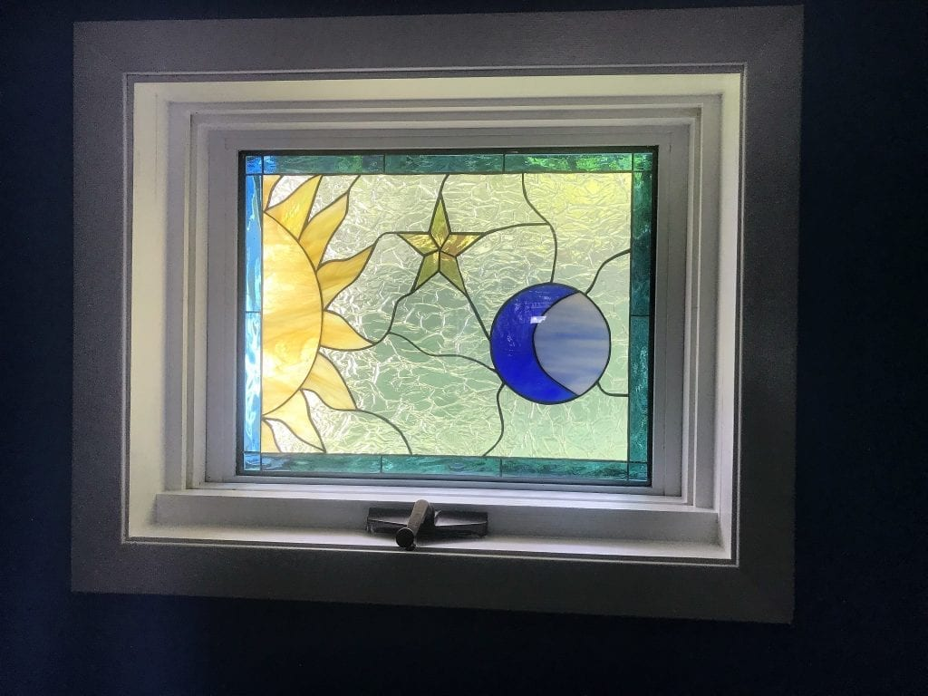 Mystical sun, moon, and star window installed in a crank-out vinyl frame