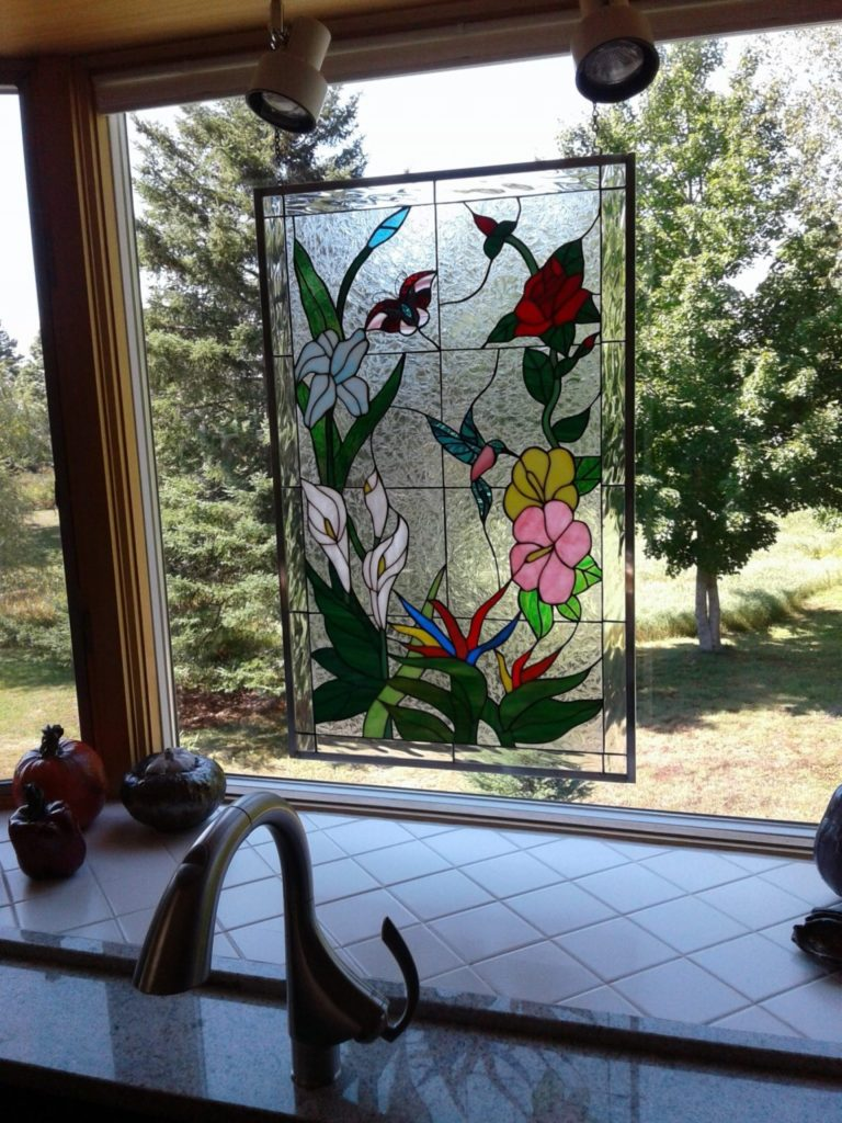Lovely colorful hummingbirds and flowers stained glass panel hung in a kitchen window with chain