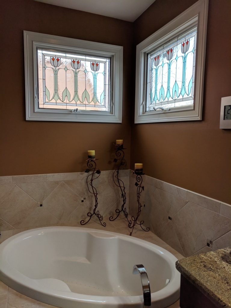 Elegant Crank-out stained glass English tulip windows installed in a bathroom