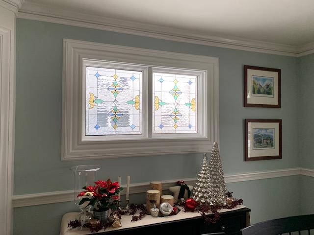 Two Beautiful Pastel Colored Stained Glass Windows Installed In Vinyl Frames In A Dining Room